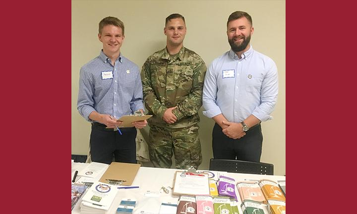 Law students in photo assisting the soldier are Jared Harsha and Daniel Sloat; the soldier is PFC (Private First Class) Harrack